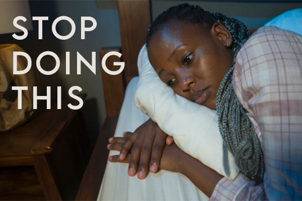 Woman laying in bed with a worried look - catastrophic thinking