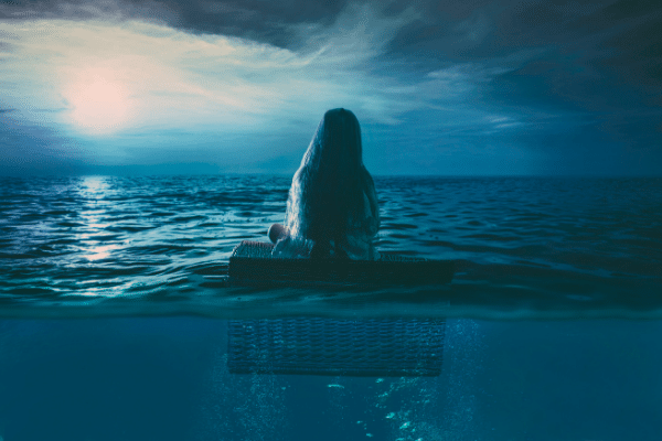 The Subconscious Mind - Young girl is floating on the ocean late at night with a full moon on the horizon.